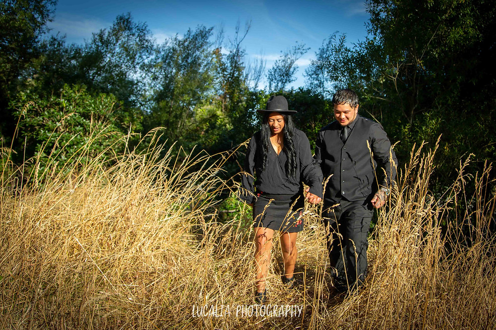 engaged couple walking through long grass during golden hour, Wairarapa wedding photographer