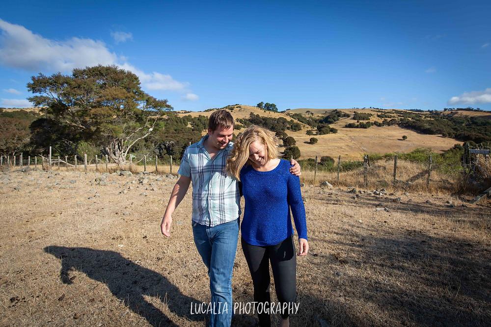 engaged couple hugging with hills in background, Martinborough Wairarapa wedding photographer