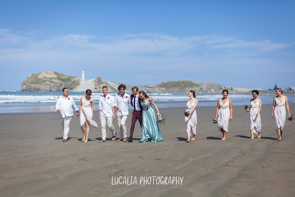 wedding party walking along the beach with lighthouse, Castlepoint Wairarapa wedding, Lucalia Photography