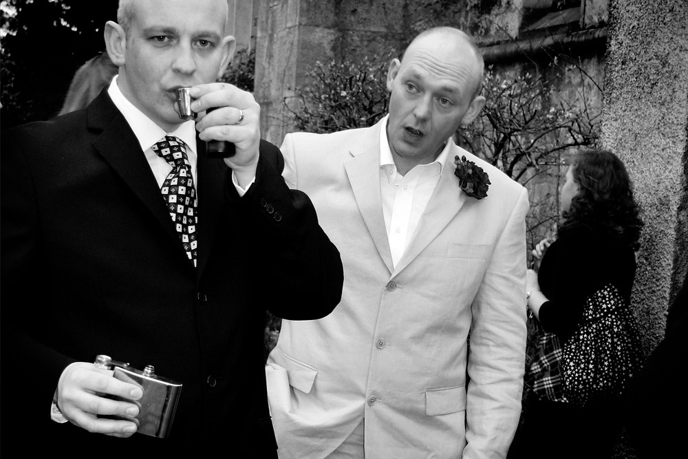 groom looking in surprise at his best man drinking whiskey from a hip flask before his wedding