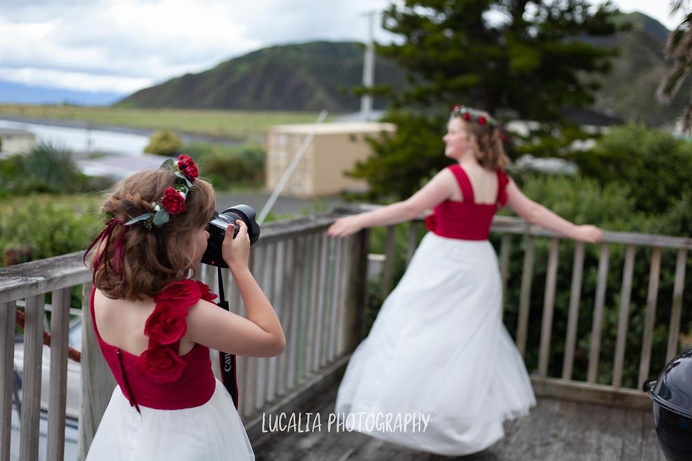 junior bridesmaid taking a photo of dancing sister, Ngawi Wairarapa wedding photographer
