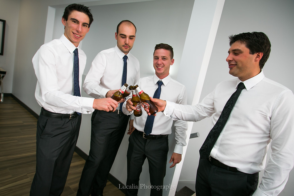 groom and groomsmen saying cheers