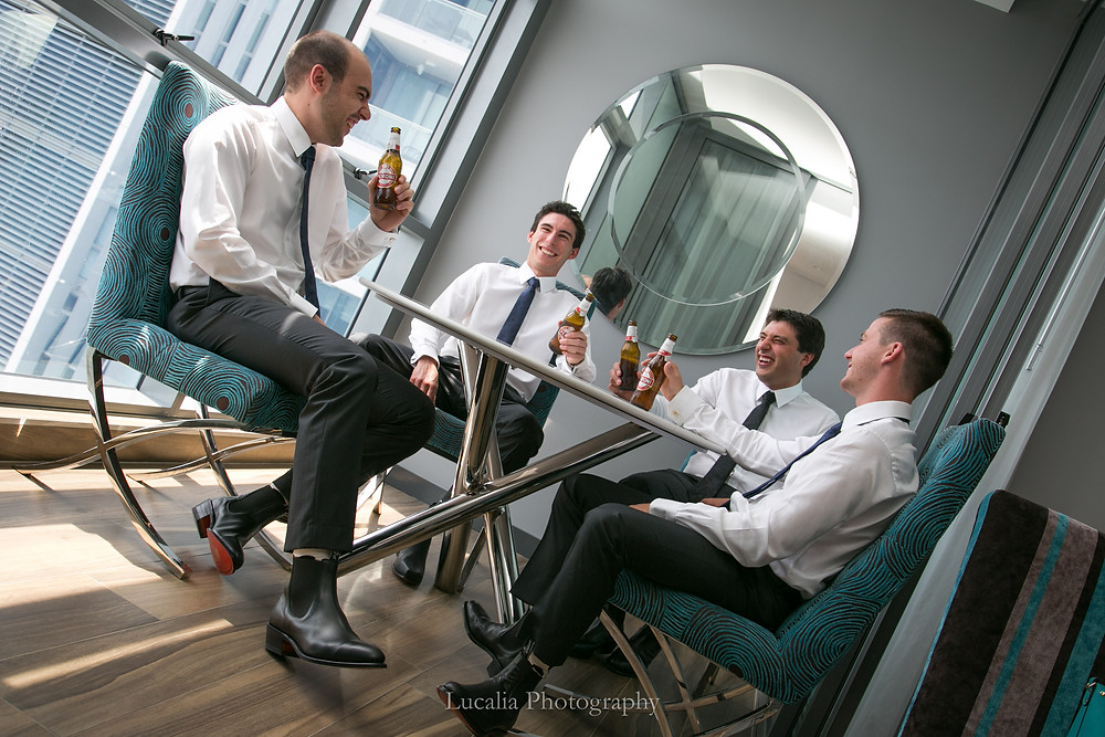 groom and groomsmen sitting at a table drinking Peroni beer