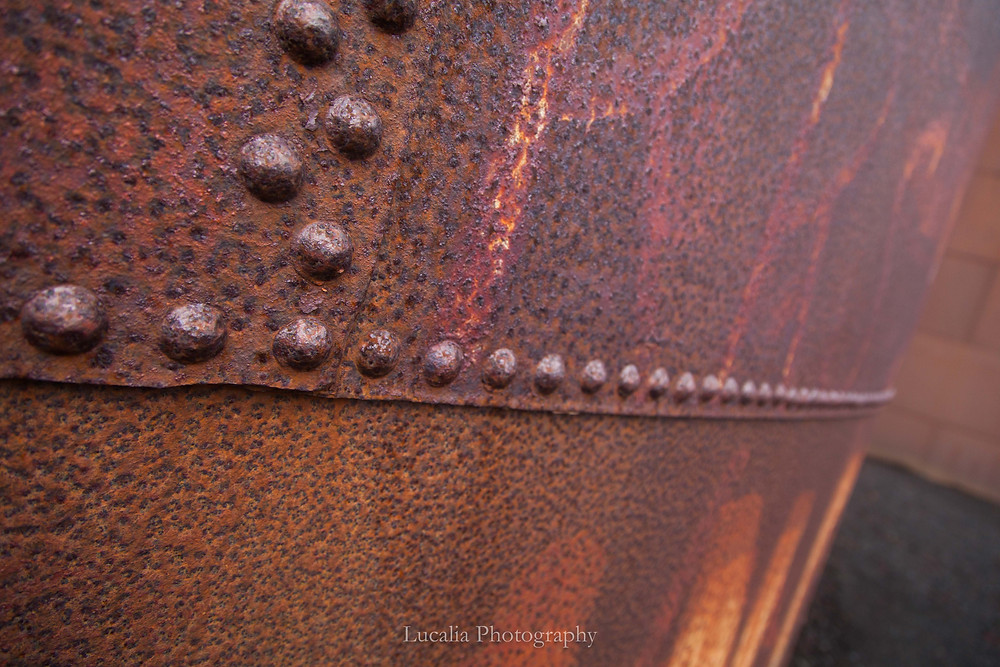 A detailed photograph of rusted rivets on a metal storage tank at Deception Island.