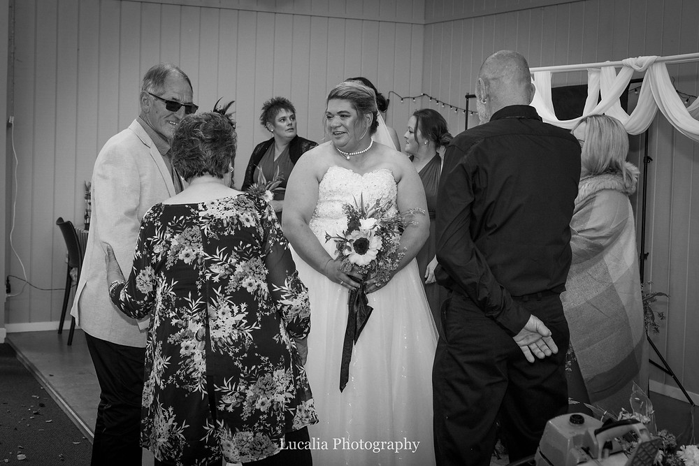 bride with groom smiles at her parents during wedding ceremony, Wairarapa wedding photographer