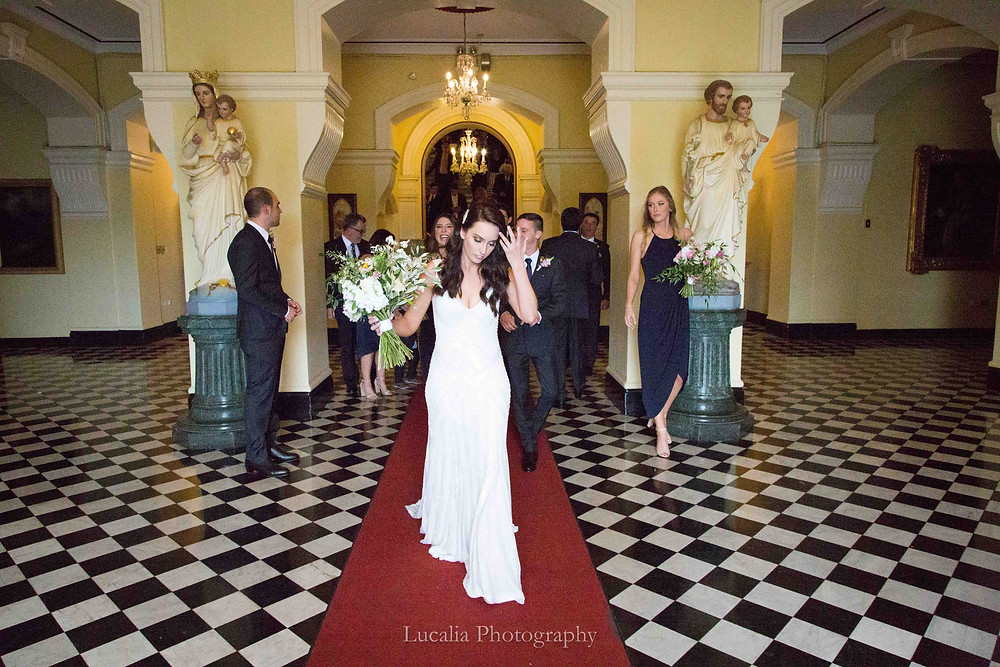 bride walking out of a church with bridal party behind in NSW