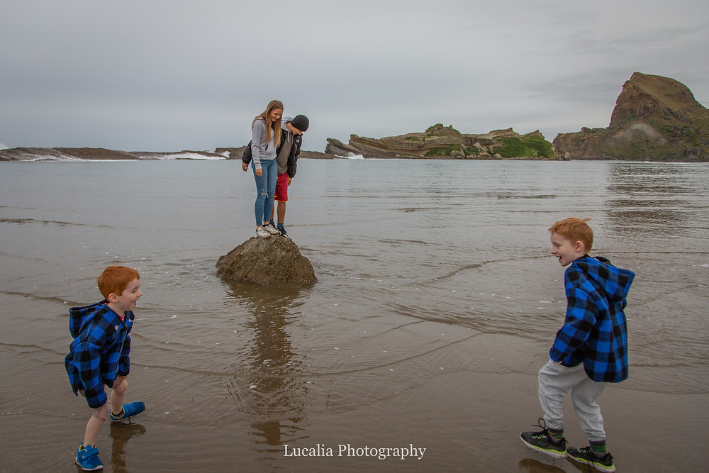 children standing on a rock in the water, Castlepoint Wairarapa family photographer