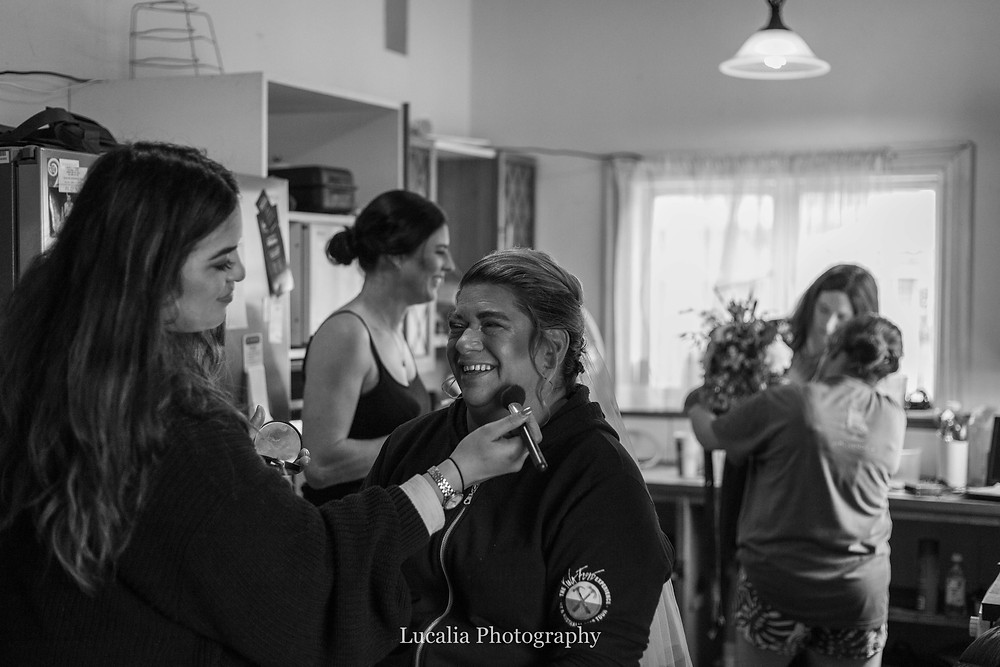 bride getting her makeup done with bridesmaids in the background, Wairarapa wedding photographer