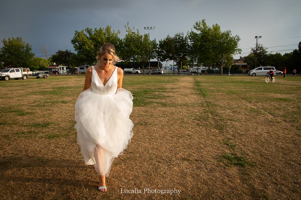 bride walking across a field in golden light, Wairarapa