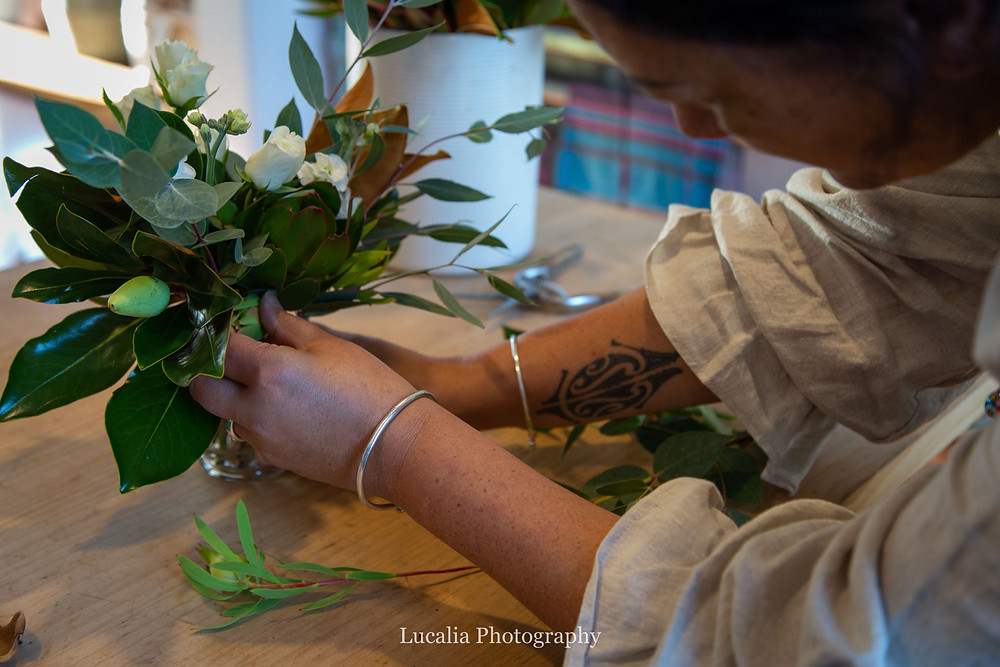 florist adjusting green foliage in a vase, Wairarapa