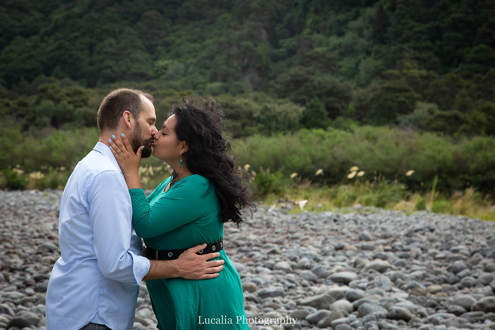 engaged couple kissing on riverbed, Wairarapa