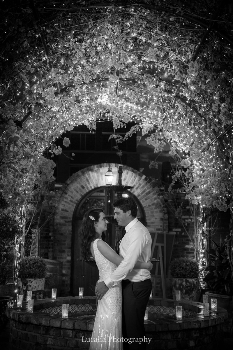bride and groom hugging underneath lit up arbour, Wairarapa wedding photographer