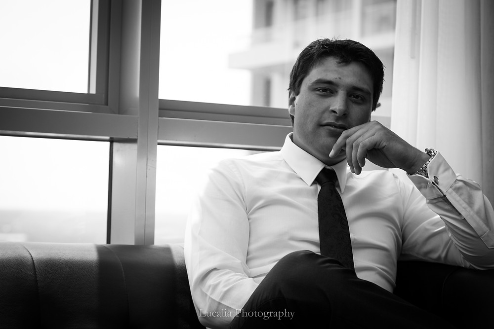 groom sitting on a sofa with his hand to his chin