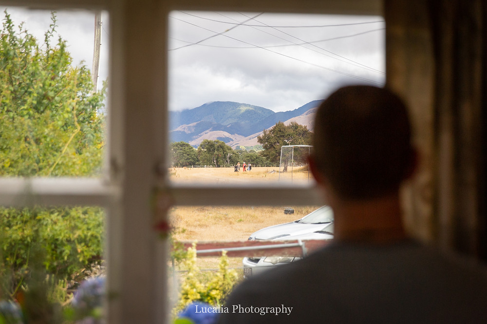 looking out the window at arriving wedding guests, Wairarapa wedding photographers