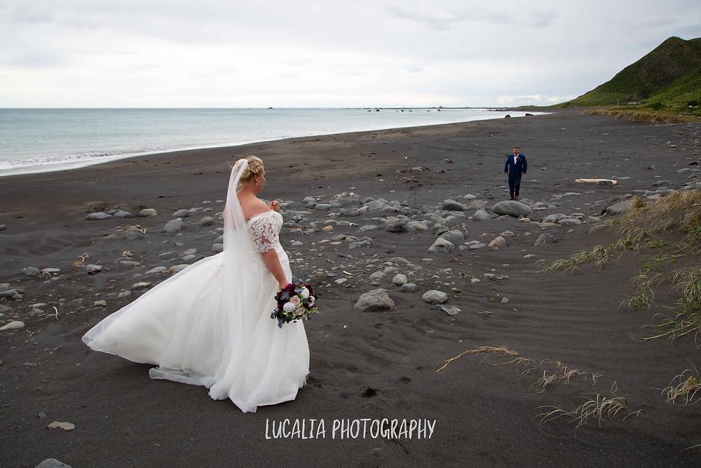 bride watching groom walking along black sand beach at Ngawi, Wairarapa wedding