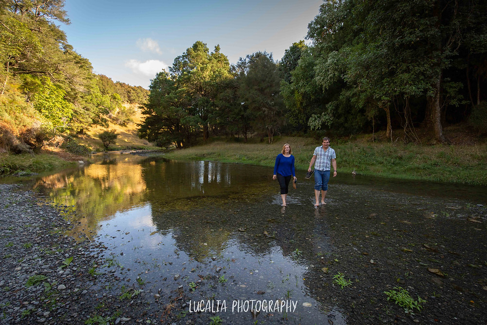 couple walking across a river valley in bare feet, Martinborough
