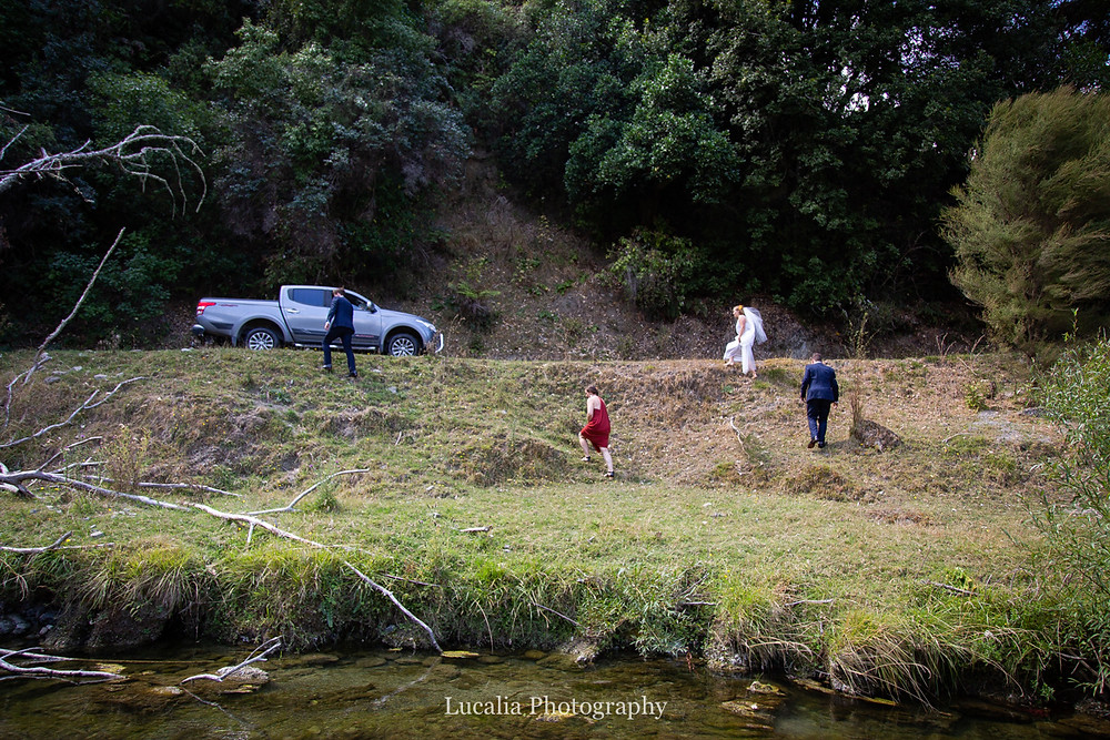 wedding party walking back up river bank to ute, Wairarapa wedding photographers