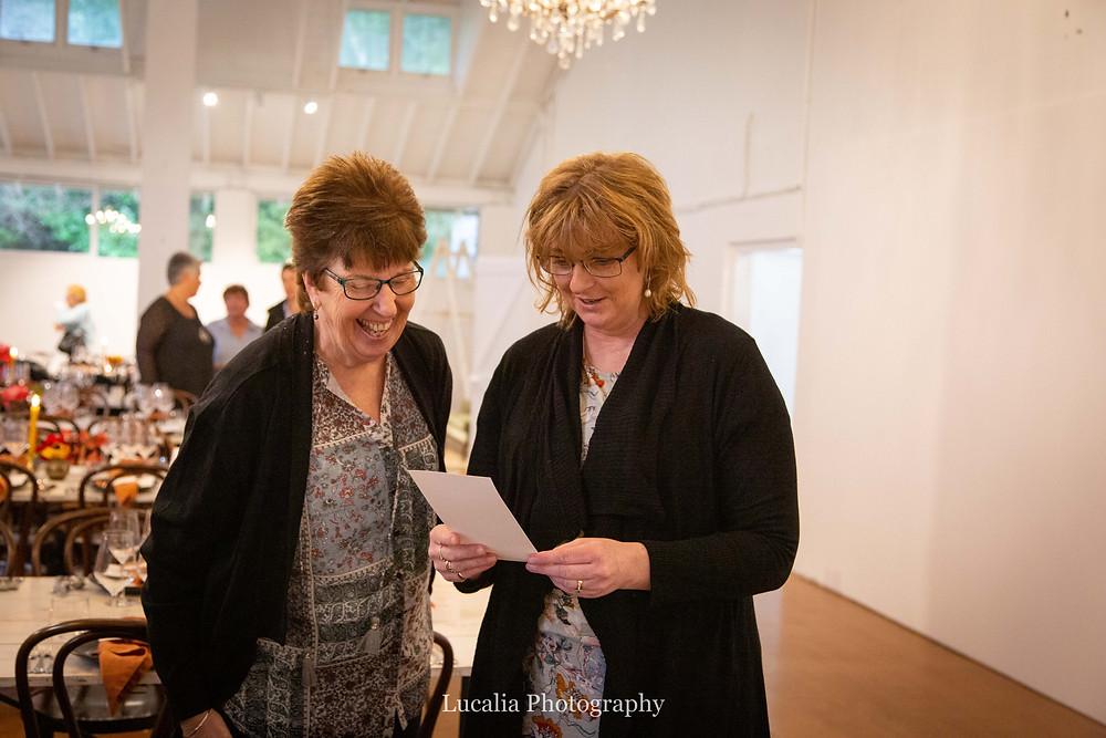 guests smiling looking at menu Rose & Smith at Tauherenikau Wairarapa wedding venue