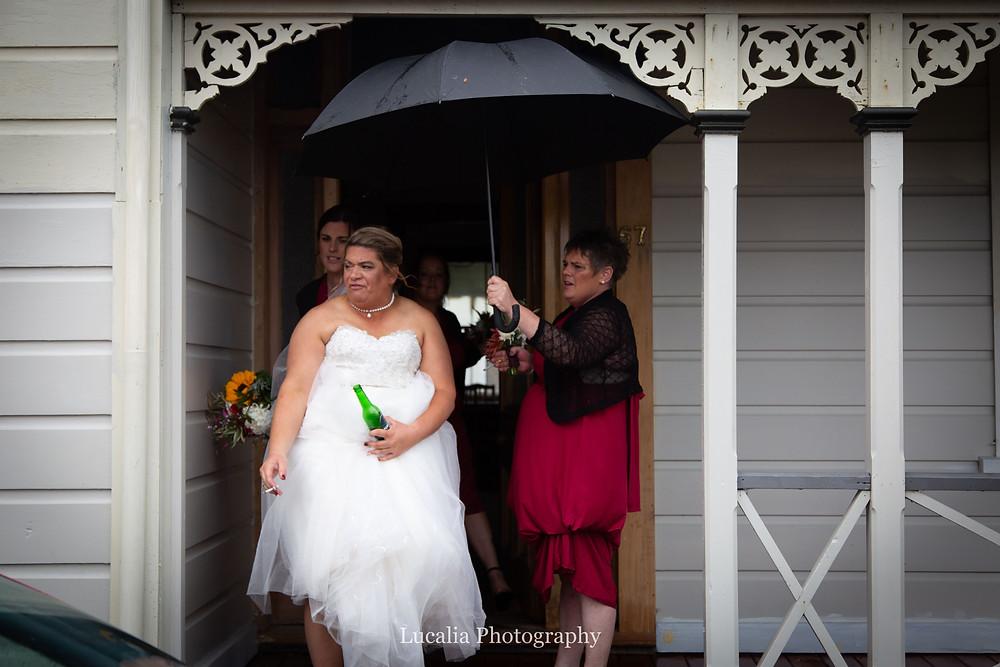 bride looking disappointed underneath umbrella, Wairarapa wedding photographer