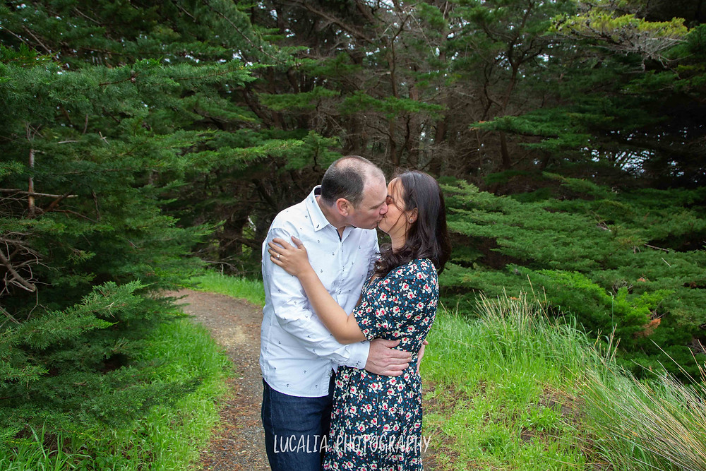 engaged couple kissing in pine forest, Castlepoint, Lucalia Photography Wairarapa wedding photographer