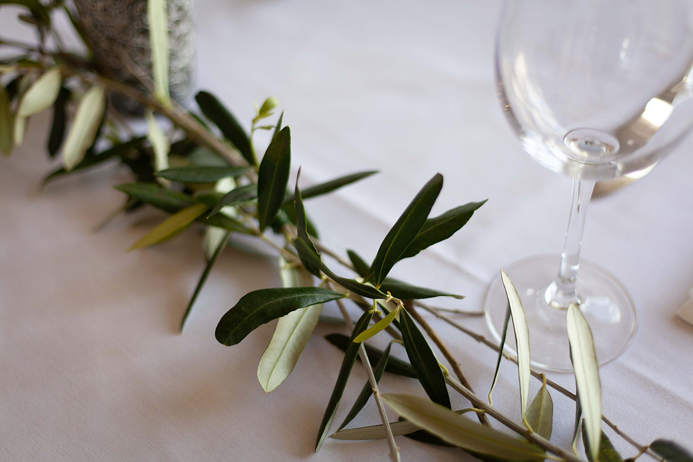 wedding reception detail olive branches, white linen and wine glass, Olivio~nor, Martinborough, Wairarapa wedding venue