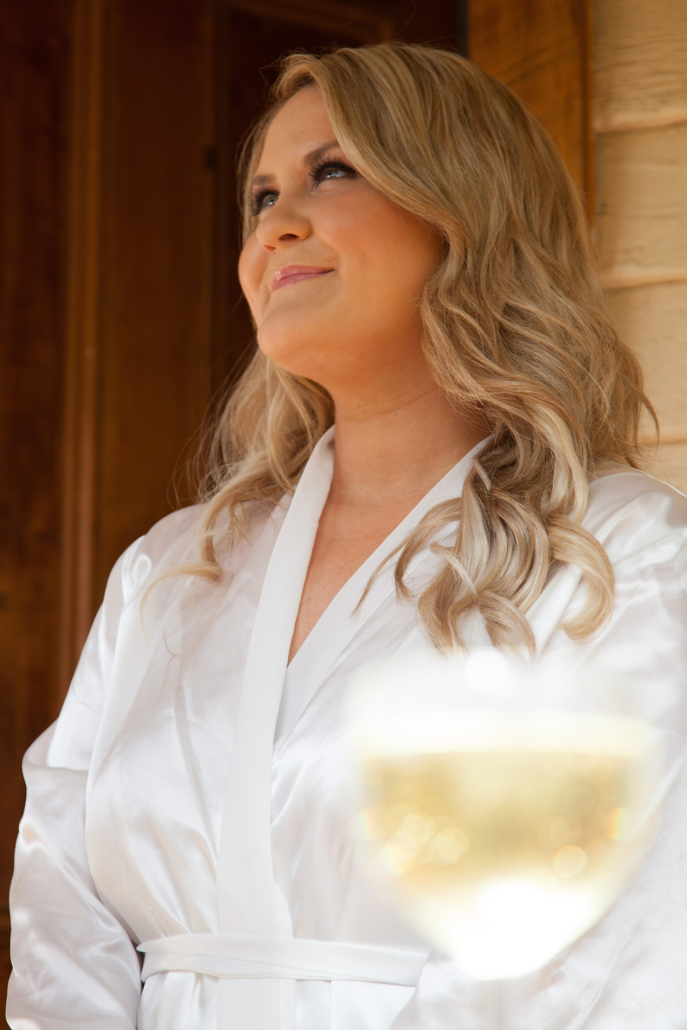 bride-to-be relaxing outside with a glass of white wine whilst getting ready for her wedding