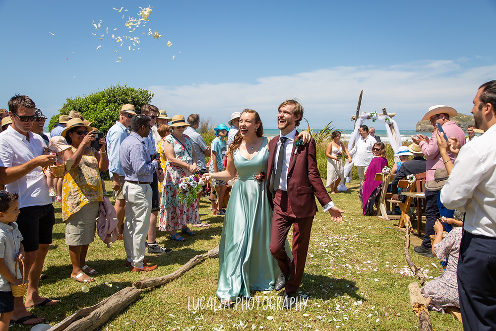 married couple walking down the aisle at their wedding in the summer sun, Castlepoint Wairarapa, Lucalia Photography