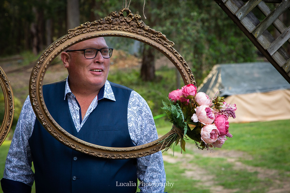 male wedding guest smiling behind a suspended picture frame with flower, Wairarapa weddings