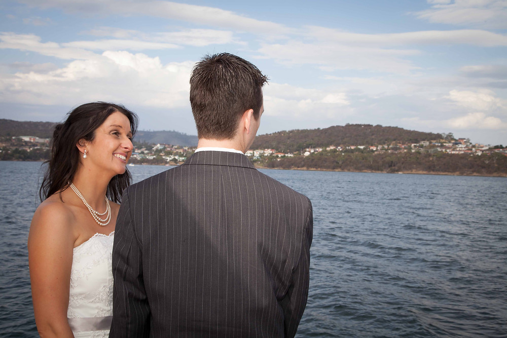 bride looking at her groom whilst on a boat with the ocean and hills in the background