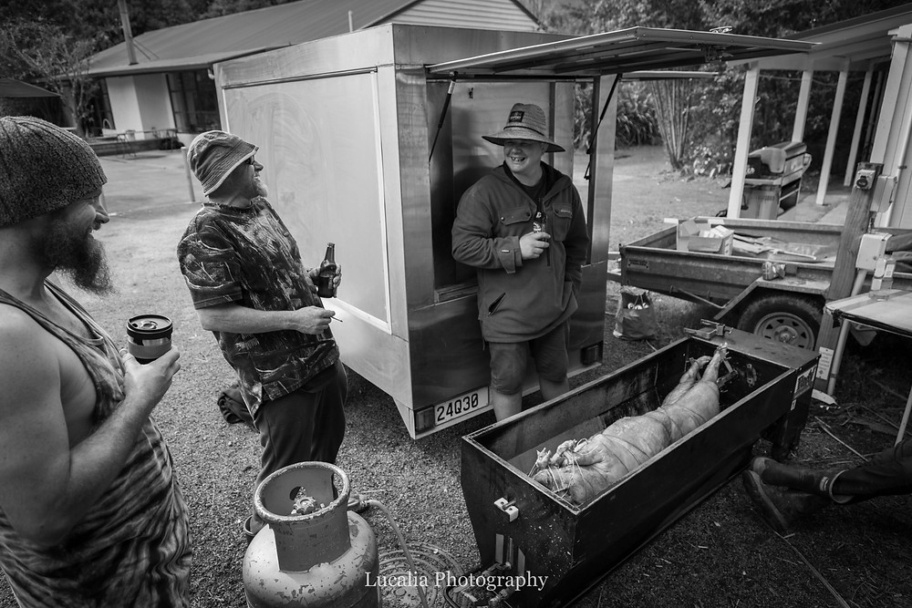 groom and groomsmen gathered around pig on a spit, Wairarapa wedding photographer
