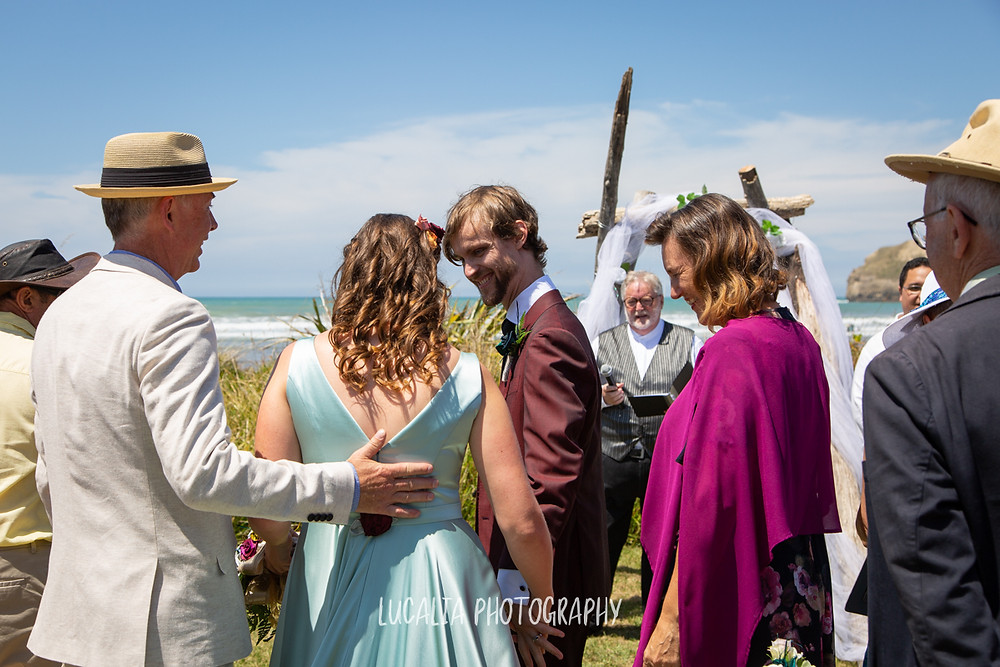 dad holding daughter with groom and mum, Castlepoint Wairarapa wedding, Lucalia Photography