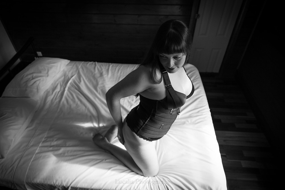Black and white lady kneeling on a bed wearing black lingerie looking over her shoulder. Natural light boudoir portrait