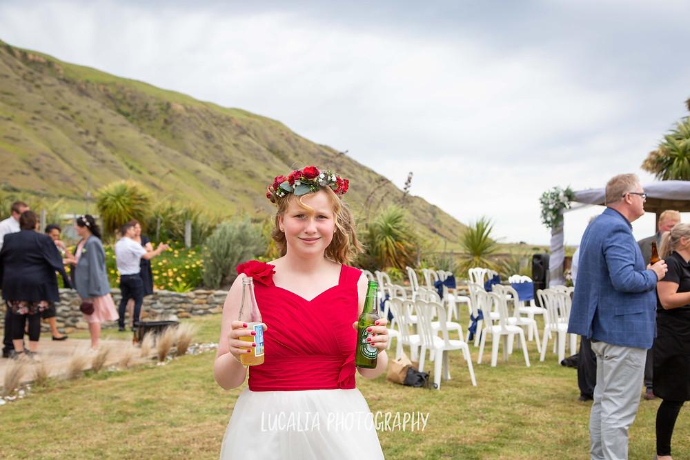 junior bridesmaid holding beers, Waimeha Camping Village wedding venue, Ngawi, Wairarapa wedding