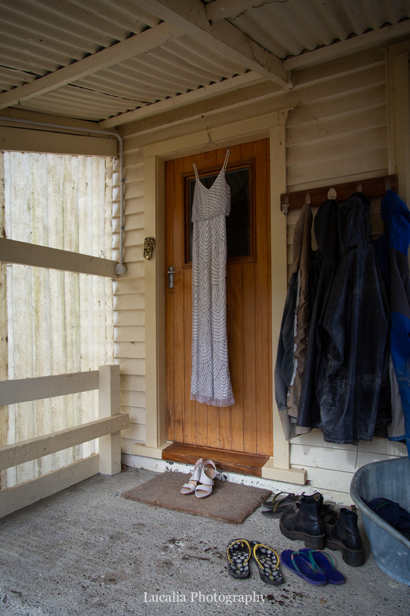 wedding dress and shoes hanging in front doorway with farm coats and boots, Wairarapa wedding photographers