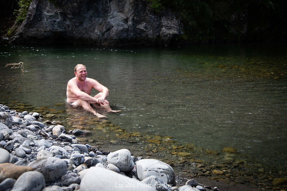 dad sitting in river after swimming, Tararua Forest Park, Wairarapa family photographer
