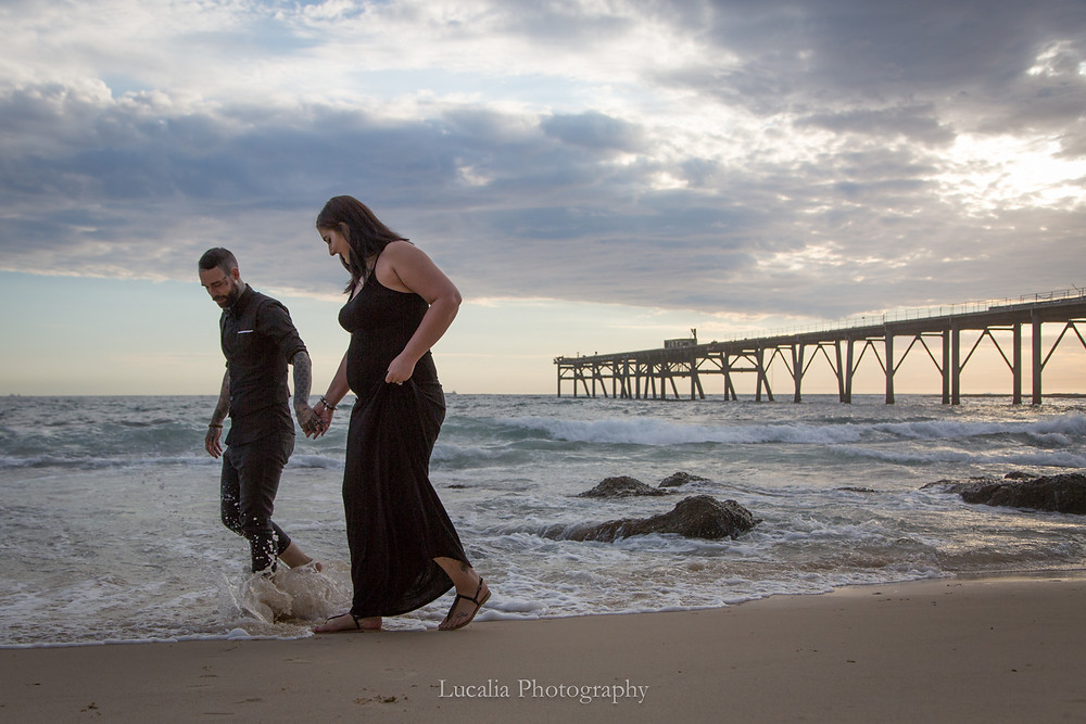 engagement photo of a couple wearing black walking along the waters edge at the beach, Wairarapa
