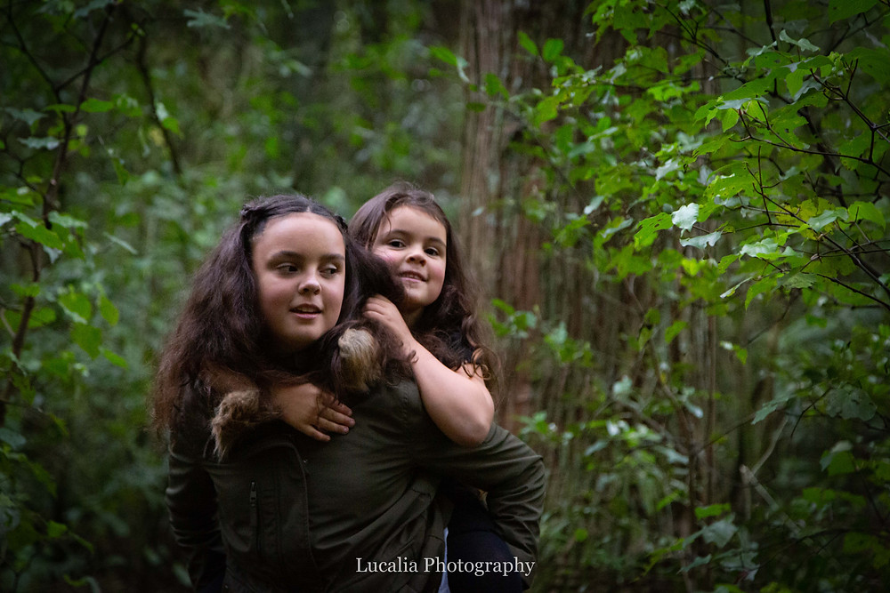 older sister giving younger sister a piggy back in a forest, Wairarapa family photographer