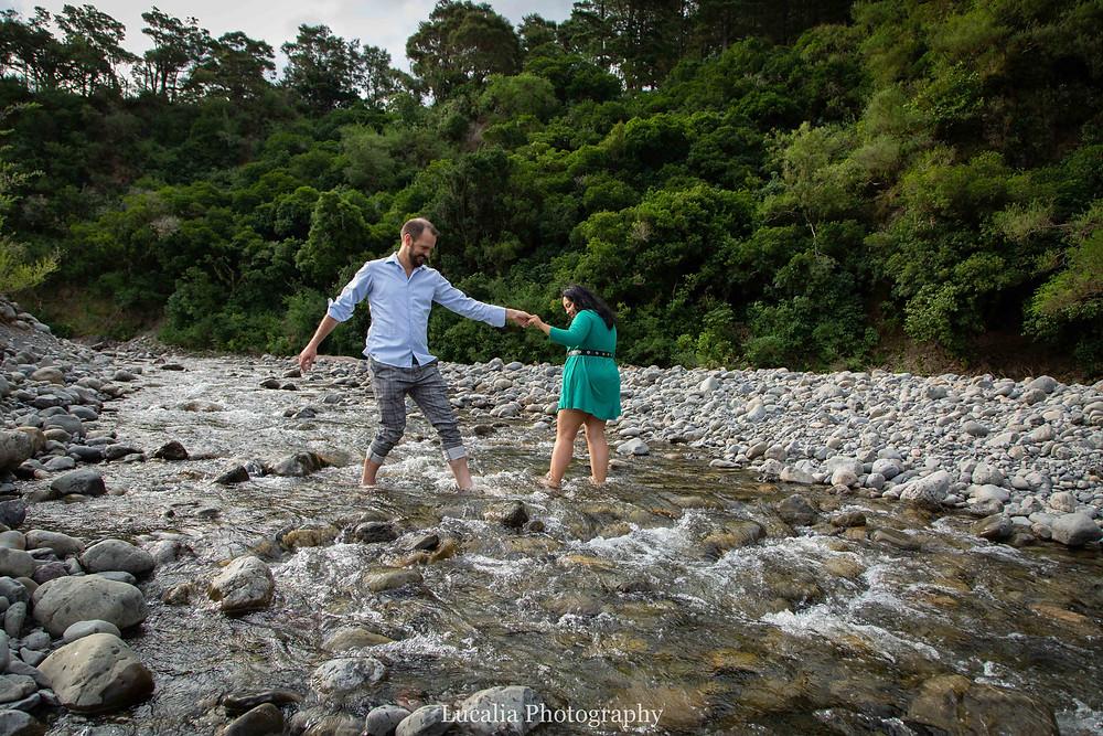 engaged couple walking across a river, Wairarapa