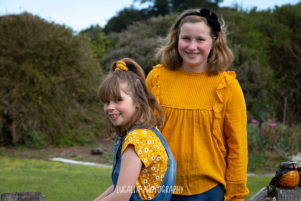 two  sisters wearing yellow tops in a garden, Wairarapa wedding photographer