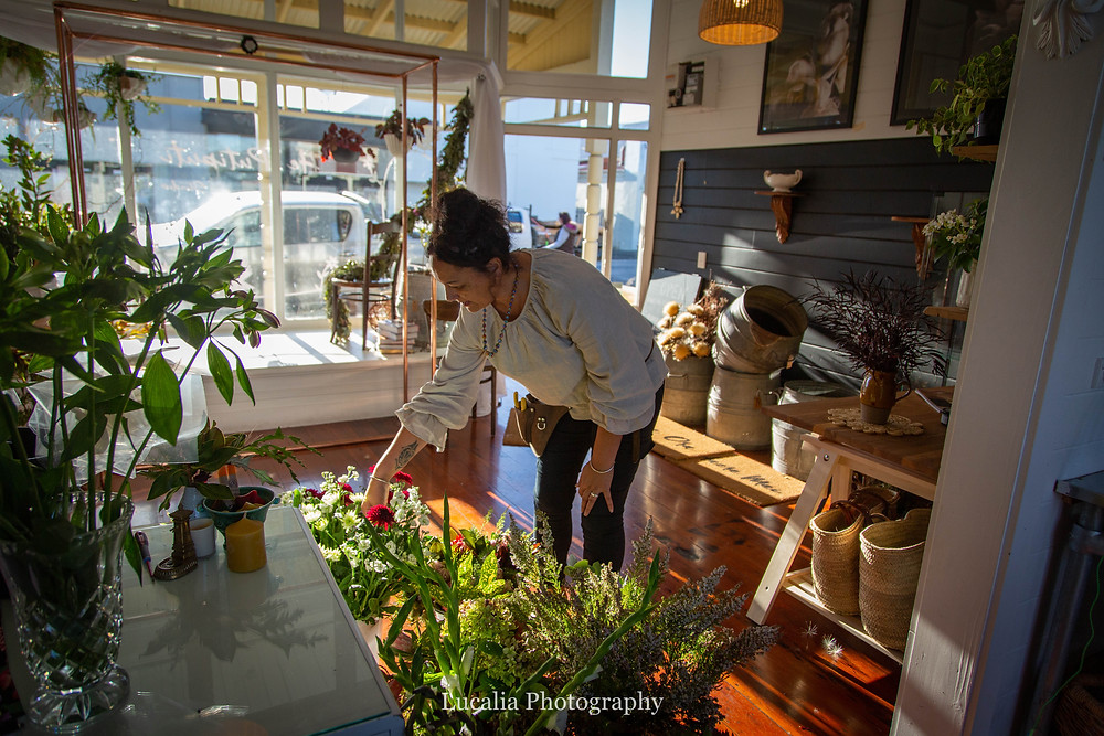 florist bending down to touch flowers in her studio, Wairarapa