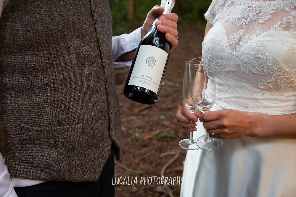 bride and groom with Le Gra sparkling wine, Kiriwhakapapa Wairarapa wedding photographer