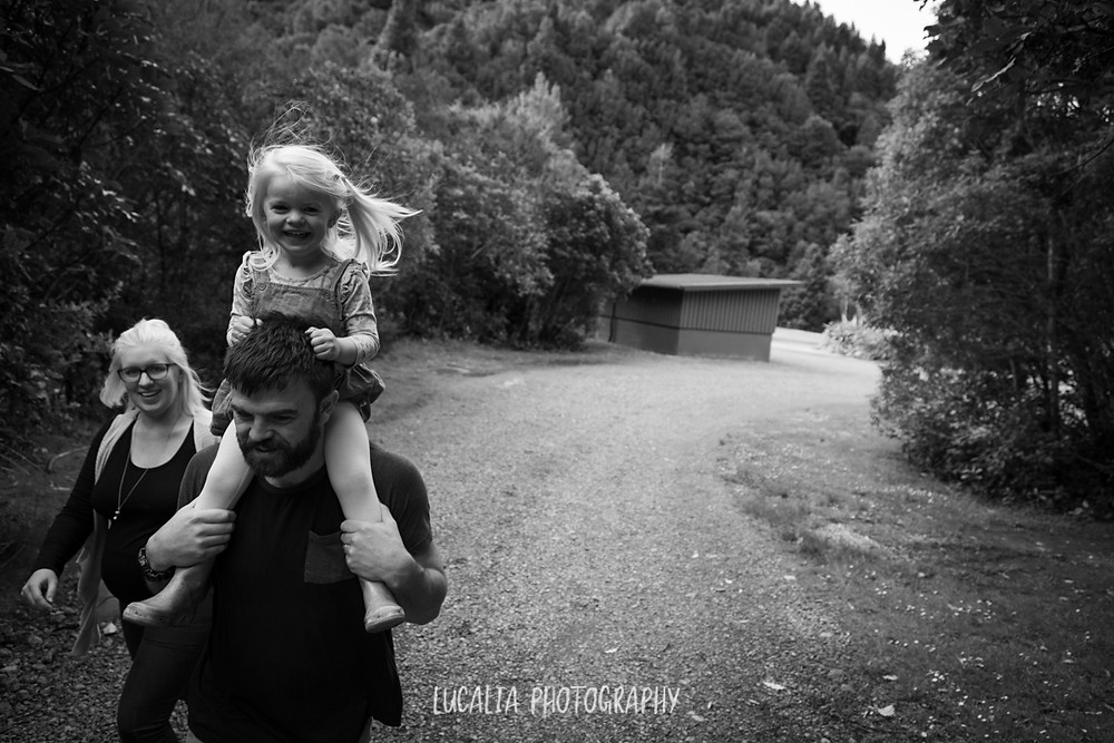 daughter riding on her dad's shoulders walking with mum down bush path, Kiriwhakapapa, Wairarapa family photographer