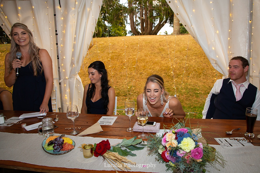 bride laughing during speeches at marquee wedding, Wairarapa