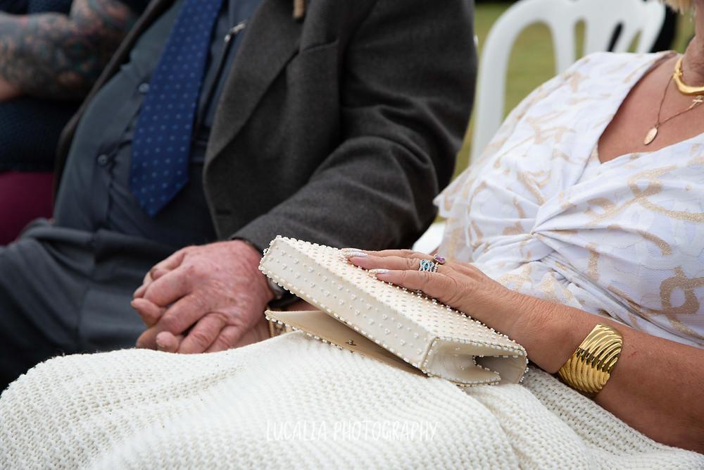 mum and dad holding hands at daughter's wedding ceremony, Waimeha Camping Village, Ngawi, Wairarapa wedding