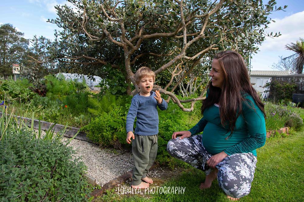 pregnant mum smiles at son eating herbs outside, Wairarapa maternity photographer