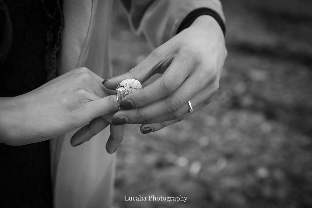 fiancée putting a shell on her finger like a ring, Cape Palliser, Wairarapa