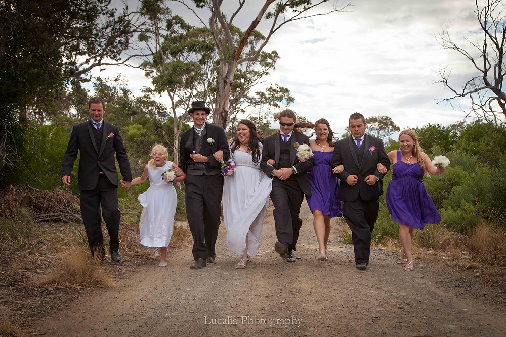 wedding party walking on a dirt road in the bush