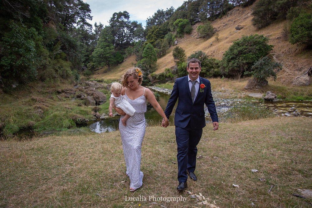 wedding couple with daugher walking near river holding hands, Wairarapa wedding photographers