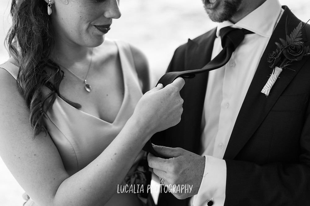 bride looks at groom's tie, Castlepoint Wairarapa wedding, Lucalia Photography