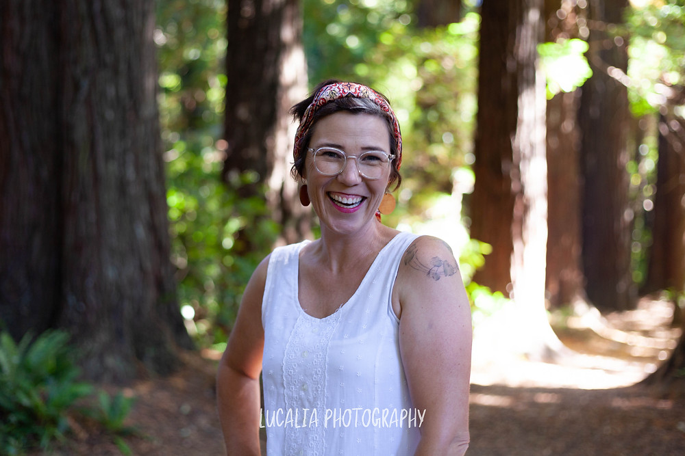 Wairarapa wedding celebrant Aingie Miller smiling in the Redwoods at Pūkaha National Wildlife Centre